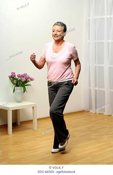 older woman doing gymnastics - knee lift - senior