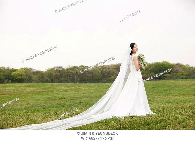 a woman posing in a wedding dress in the nature