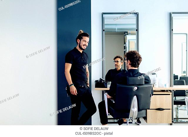 Male hairstylists chatting in hair salon