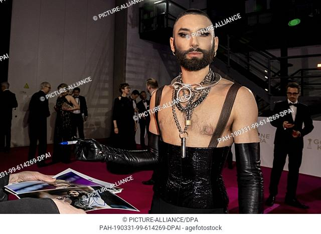 "30 March 2019, Berlin: Conchita Wurst, Thomas """"Tom"""" Neuwirth, signs autographs on the red carpet before the Golden Camera awards ceremony at Berlin's disused..."
