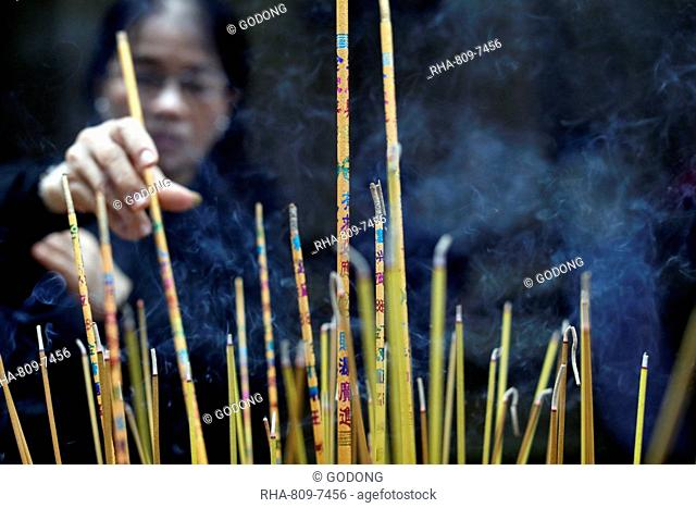 Mariamman Hindu Temple, woman burning incense sticks, Ho Chi Minh City. Vietnam, Indochina, Southeast Asia, Asia