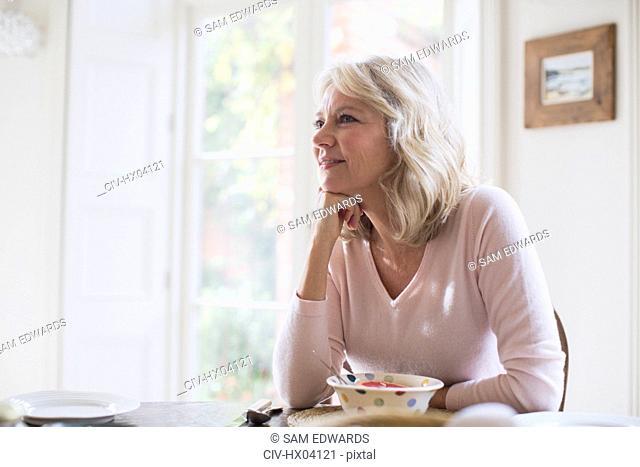 Smiling, satisfied mature woman eating breakfast