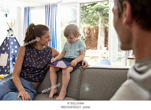 Mother watching little son using tablet at home