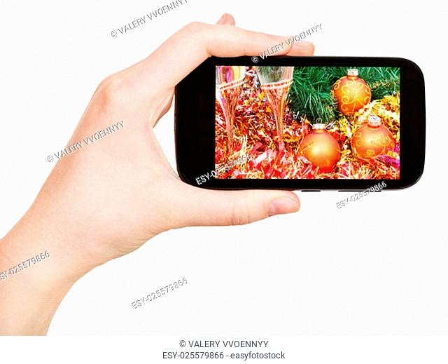 hand holds handphone with Christmas still life on screen isolated on white background