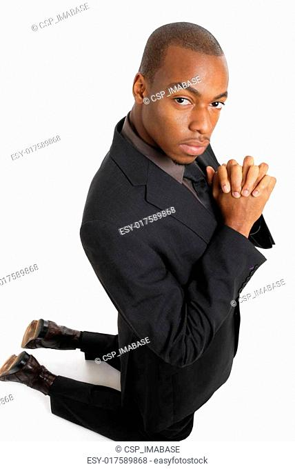 Business man kneeling doing a prayer gesture