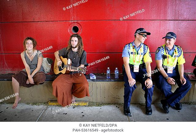 Australian Police sit next to guitar player near the conference site of the G20 summit in Brisbane, Australia, 15 November 2014