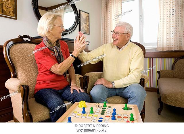 Senior couple playing ludo in nursing home, Bavaria, Germany