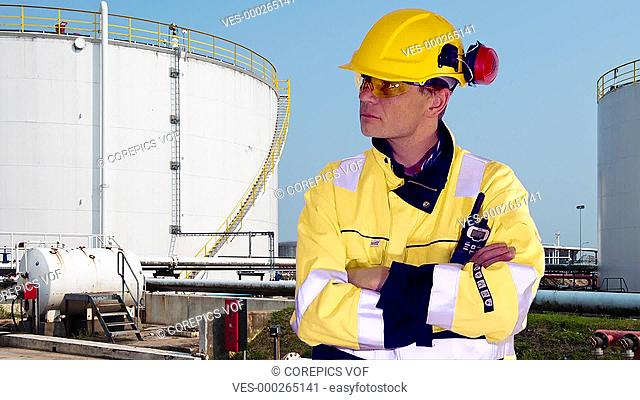 Person standing confident in front of industrial background, nodding and looking approving at camera
