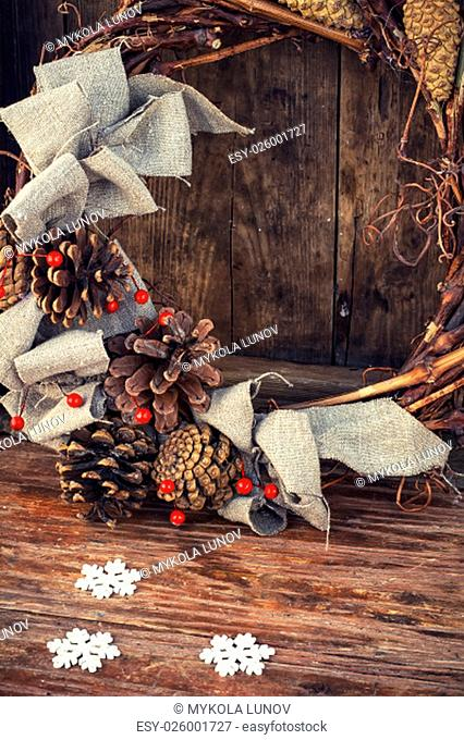 Woven from twigs and decorated with pine cones Christmas wreath on snowy wooden background