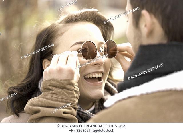 boyfriend dressing buoyant teenage girlfriend with reversed sunglasses, wrong way round, couple in Cottbus, Brandenburg, Germany