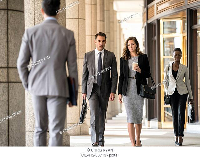 Corporate business people walking in cloister