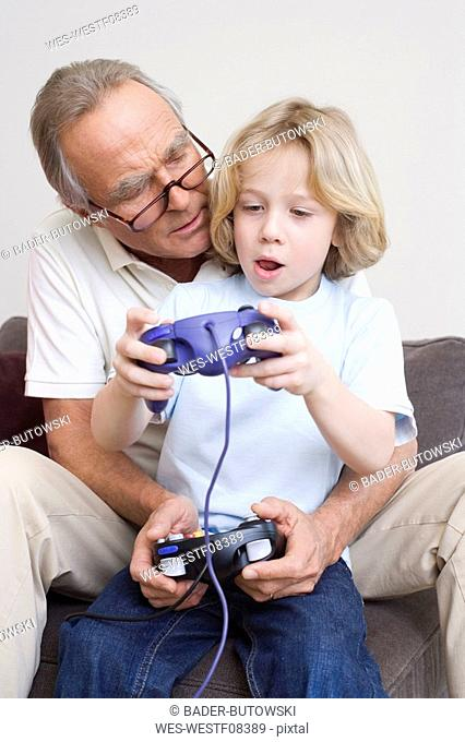 Grandfather and grandson 8-9 playing video game, portrait