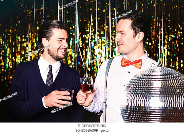 Two men at party, holding drinks