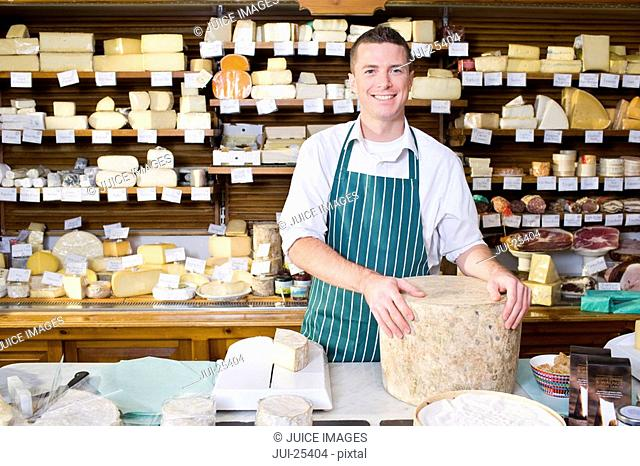 Salesman standing at counter with cheese in cheese shop