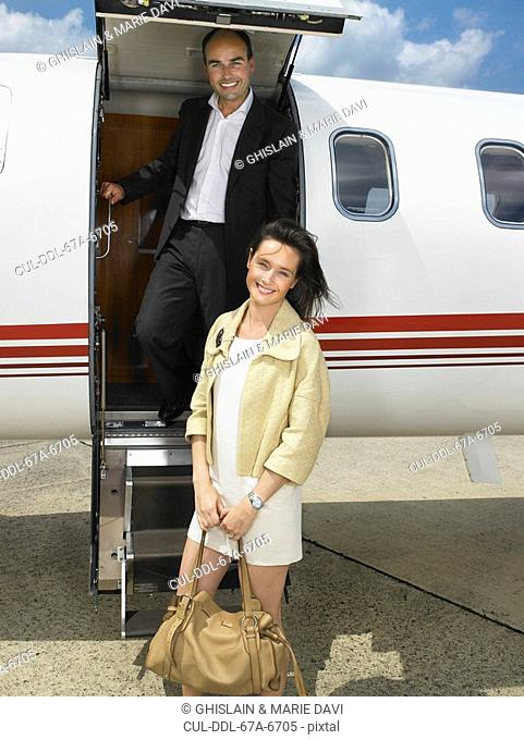 Couple getting down from private jet