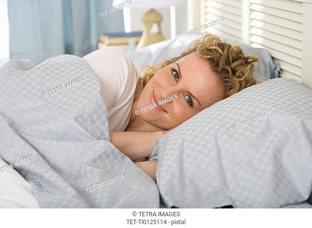 Portrait of woman laying in bed