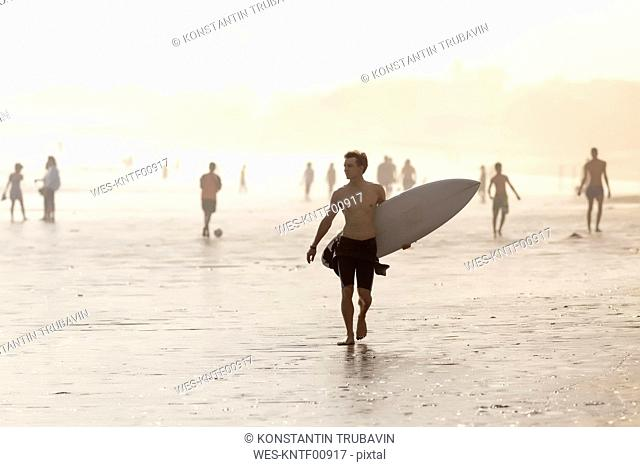 Indonesia, Bali, surfer carrying his surfboard on the beach at sunset