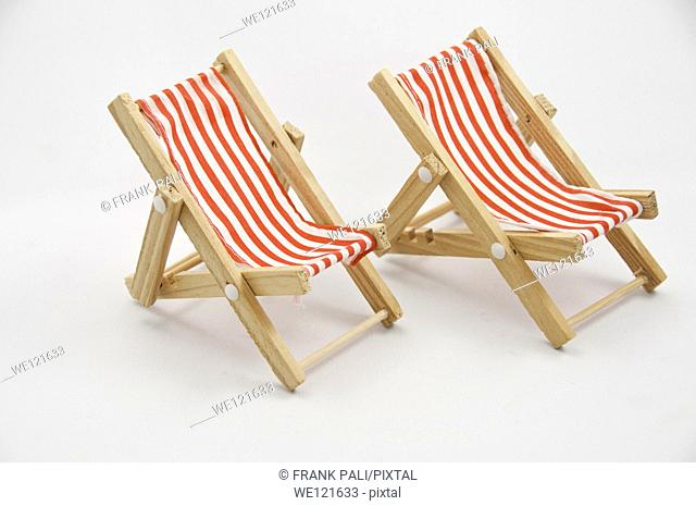 Two miniture chairs on a white background