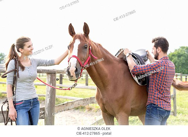 Couple saddling horse in rural pasture