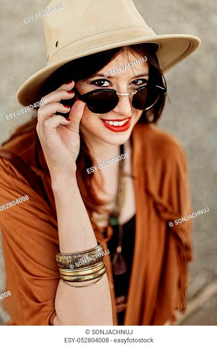 beautiful stylish hipster woman in sunglasses smiling, looking up, with windy hair. boho traveler girl in gypsy look, near beach in mountains