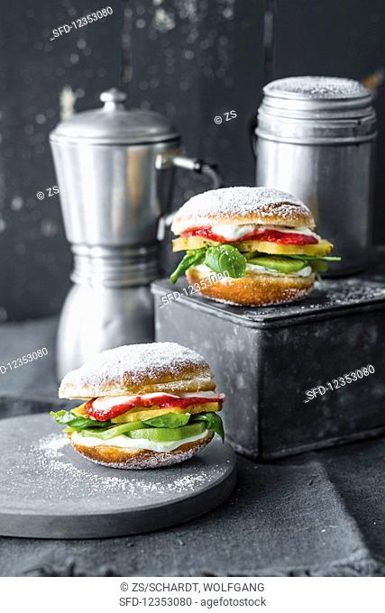 Sweet burgers: doughnuts with pineapple, kiwi, lime cream, raspberry sauce, and basil
