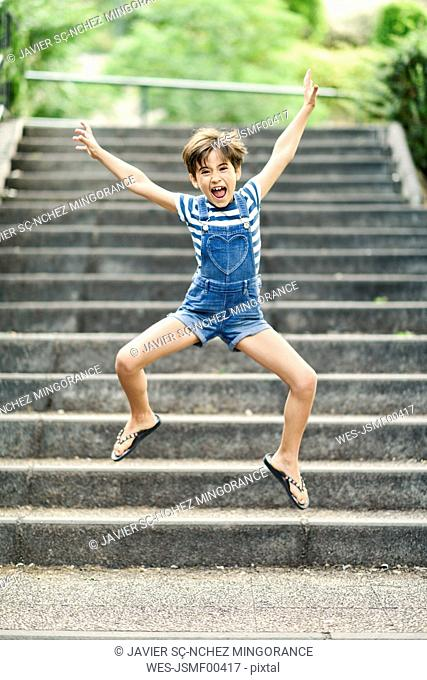 Portrait of screaming little girl jumping in the air outdoors