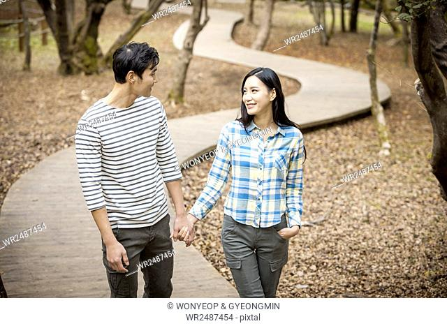 Young smiling couple walking hand in hand face to face in park