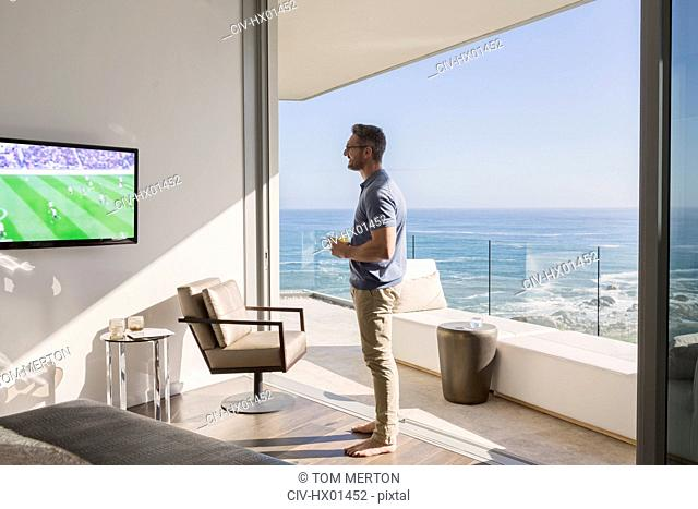 Man watching soccer on TV at sunny luxury patio doorway with ocean view