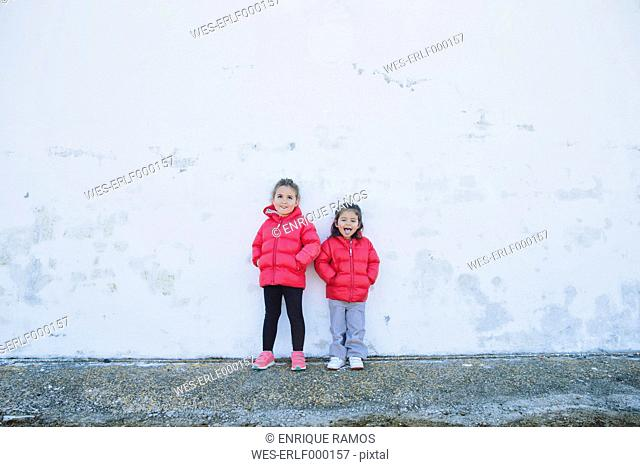 Two little girls pulling funny faces in front of a wall