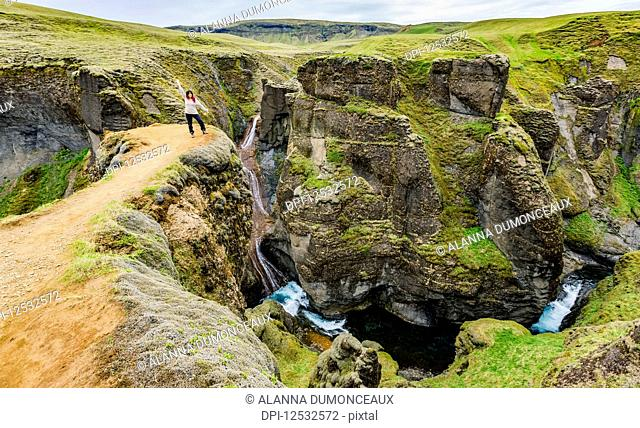 A female tourist stands on a cliff viewpoint in the picturesque valley of Fjadrargljufur in Southern Iceland; Iceland