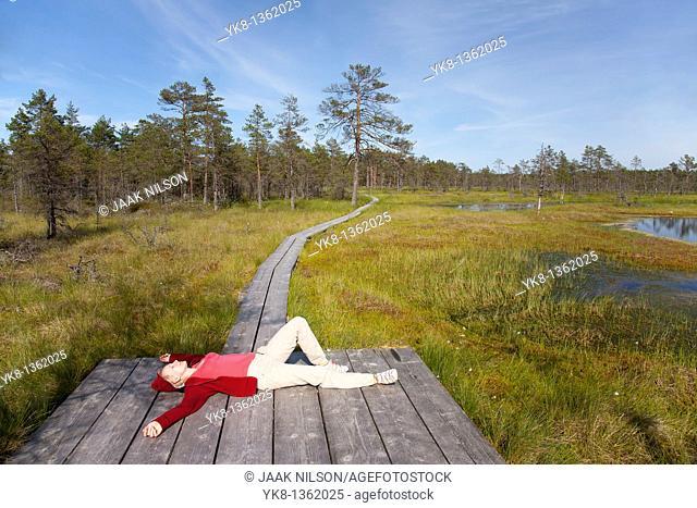 Young Woman Lying on Wooden Boardwalk in Viru Bog, Lääne-Viru County, Estonia, Europe