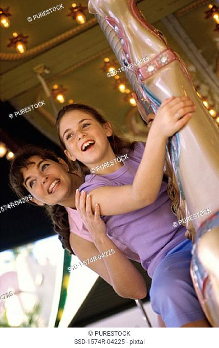 Low angle view of a girl and her mother riding on a merry-go-round