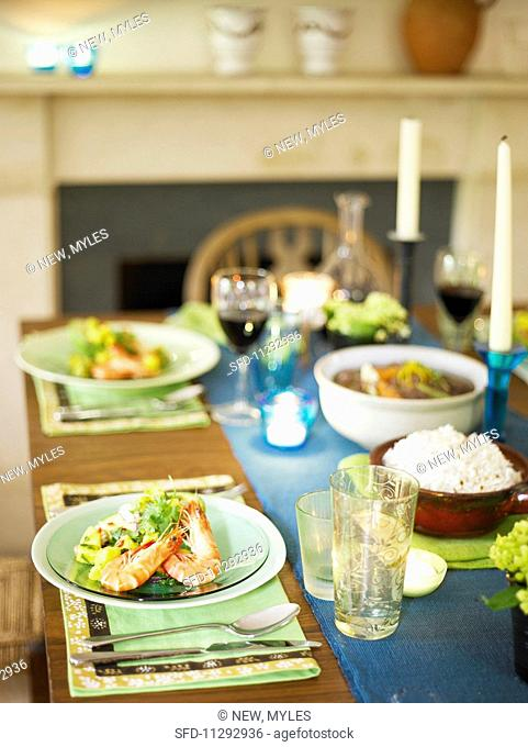 A table laden with appetisers and glasses of red wine