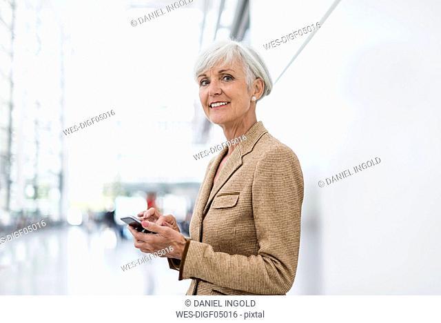 Portrait of smiling senior businesswoman using cell phone