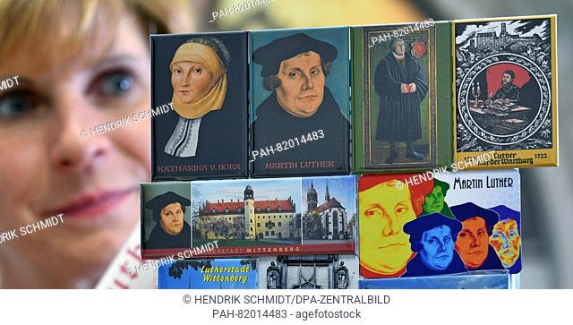 Diana Schellhaas looks at various magnets bearing images of Martin Luther and his wife Katharina von Bora, in the tourist information of Wittenberg, Germany