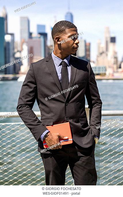 USA, Brooklyn, businessman with timetable waiting in front of Manhattan skyline