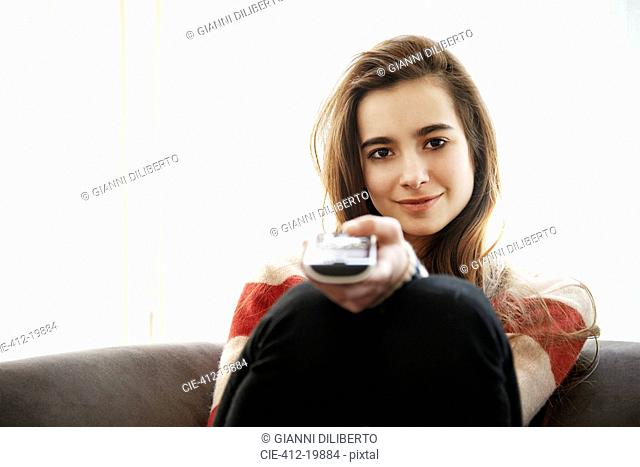 Teenage girl watching television on sofa