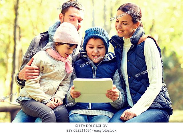 camping, tourism, hike, technology and people concept - happy family sitting on bench with with tablet pc computer at camp in woods