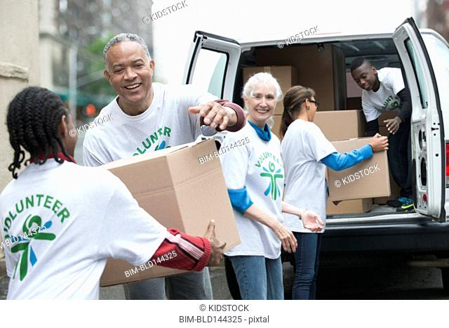 Volunteers passing cardboard boxes from delivery van