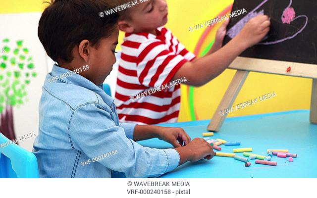 Cute little boys drawing on mini chalkboard