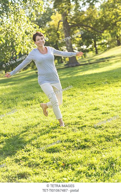 Mature woman jumping on grass