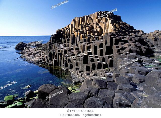 Interlocking basalt stone columns left by volcanic eruptions. View across the main and most visited section of the causeway with the coastline seen behind