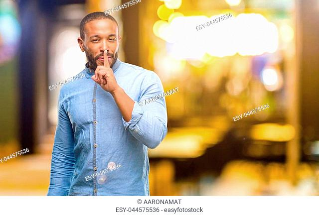 African american man with beard with index finger on lips, ask to be quiet. Silence and secret concept at night
