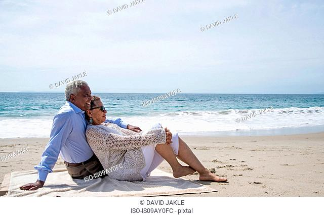 Senior couple relaxing together on beach, looking at view