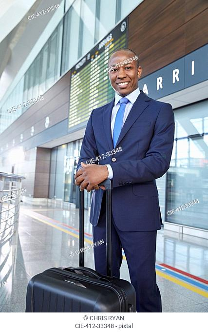 Portrait confident businessman with suitcase in airport concourse
