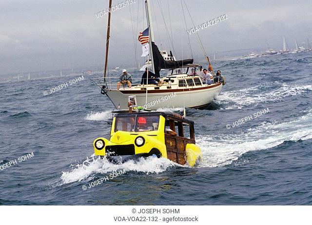A car-boat races up ahead of a sailboat during the 1992 America's Cup race near San Diego, California