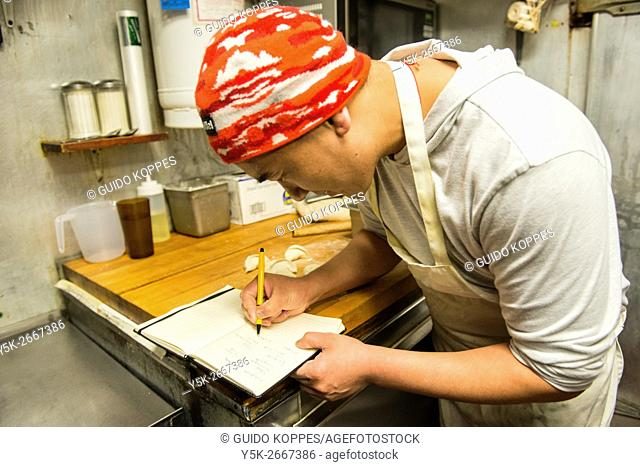 New York City, USA. Immigrant Sherpa chef from Nepal working inside a restaurants kitchen at Roosevelt Avenue, Queens