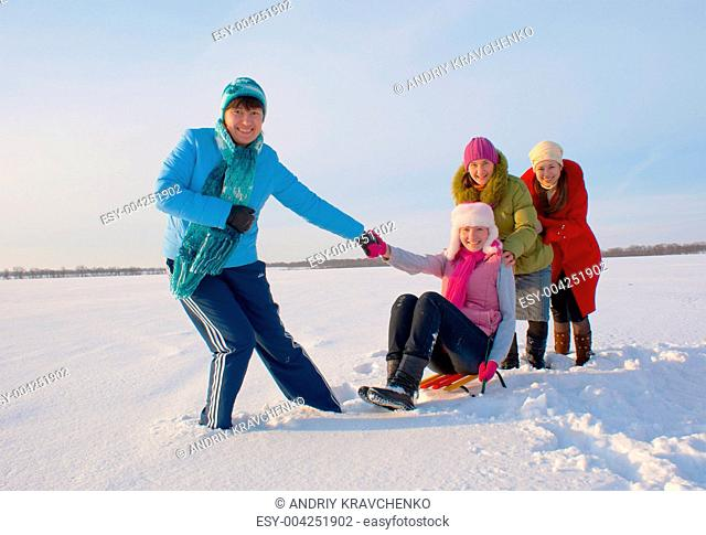 Four happy ladies sledding at winter time