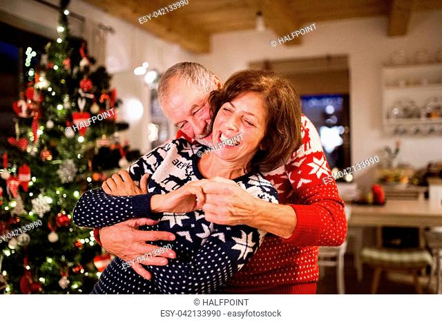 Beautiful senior couple in woolen sweaters with nordinc pattern at Christmas time, hugging. Man and woman having fun