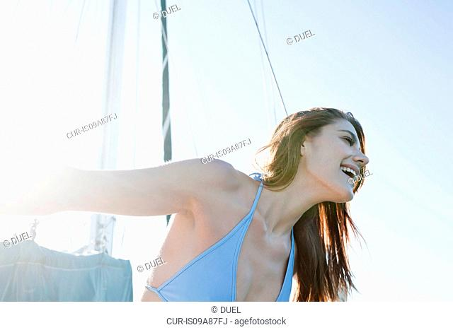 Young brunette woman on yacht, laughing